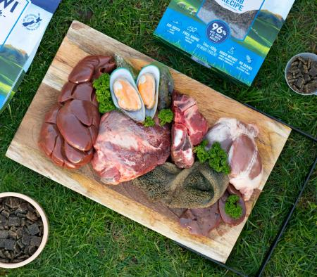 Chopping board of raw ingredients with lamb air-dried pet food